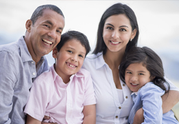Happy hispanic family portrait smiling - over a white and blue background